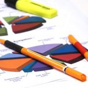 Diagramme und Stifte auf einem Schreibtisch liegend